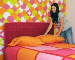 A preteen girl happily making her bed in her very colorful room.
