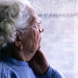 Gammal kvinna tittar ut genom fönstret